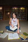 Studentessa sorridente con i libri sul pavimento delle biblioteche Fotografia Stock Libera da Diritti