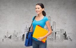 Studentessa sorridente con la borsa e le cartelle Immagini Stock