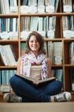 Studentessa sorridente contro lo scaffale per libri che legge un libro sul pavimento delle biblioteche Fotografia Stock