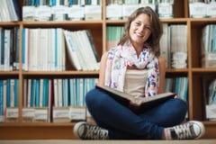 Studentessa sorridente contro lo scaffale per libri che legge un libro sul pavimento delle biblioteche Immagine Stock Libera da Diritti
