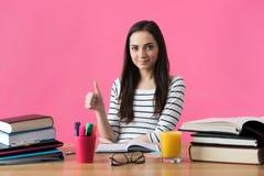 Studentessa sorridente felice che si siede al suo scrittorio con i manuali Fotografia Stock Libera da Diritti