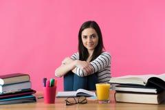 Studentessa sorridente felice che si siede al suo scrittorio con i manuali Immagini Stock Libere da Diritti