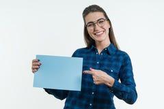 Studentessa sorridente positiva che tiene un foglio pulito di carta blu, indicante un dito alla carta immagini stock