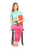 Studentessa sorridente sui libri di una tenuta della sedia Fotografie Stock Libere da Diritti