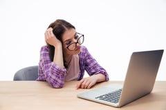 Studentessa stanca che si siede con il computer portatile Immagine Stock