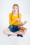 Studentessa stupita che si siede sul pavimento con il libro Fotografia Stock