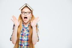 Studentessa stupita con il libro sulla testa Immagini Stock Libere da Diritti