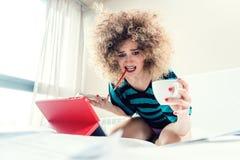 Studentessa sul suo letto che impara per l'esame nel panico Fotografie Stock