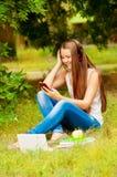 Studentessa sull'erba in cuffie con il telefono Immagine Stock