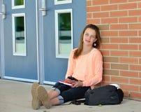 Studentessa sveglia che si siede davanti alla scuola Fotografia Stock Libera da Diritti