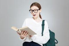 Studentessa sveglia sorpresa in vetri con il libro di lettura dello zaino Immagine Stock Libera da Diritti