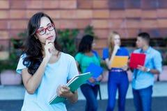 Studentessa tedesca nerd di pensiero con il gruppo di studenti immagini stock