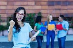 Studentessa tedesca nerd incoraggiante con il gruppo di studenti fotografia stock