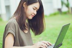 Studentessa teenager asiatica sveglia che per mezzo del computer portatile Immagini Stock Libere da Diritti