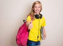 Studentessa teenager in maglietta gialla con lo zaino e le cuffie Fotografia Stock Libera da Diritti