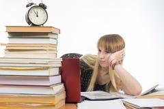 Studentessa triste che si siede ad uno scrittorio con la grande pila di libri e che esamina il computer portatile Immagine Stock