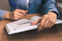 Studentessa in una camicia blu del denim che si siede ad una tavola di legno e Fotografie Stock