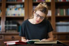 Studentessa in una lettura delle biblioteche su un desktop Immagini Stock
