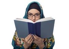 Studentessa Wearing Hijab Reading un libro Immagine Stock