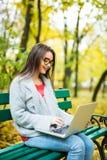 studentesse che lavorano al computer portatile nel parco di autunno Immagini Stock Libere da Diritti