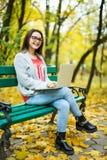 studentesse che lavorano al computer portatile nel parco di autunno Fotografia Stock Libera da Diritti