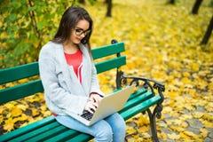 studentesse che lavorano al computer portatile nel parco di autunno Fotografie Stock Libere da Diritti