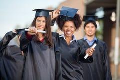Studentesse che mostrano i certificati sull'istituto universitario Fotografie Stock Libere da Diritti