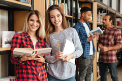 Studentesse felici che stanno in libri di lettura delle biblioteche Immagine Stock Libera da Diritti