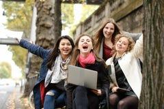 Studentesse gioconde che si siedono sul banco con l'insegnante, computer portatile, PA Fotografia Stock Libera da Diritti