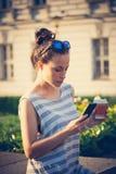 Studentflicka i stad med smartphonen och kaffe Arkivbilder
