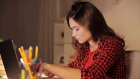 Studentflicka med bärbara datorn och anteckningsboken hemma stock video