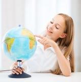 Studentflicka med jordklotet på skolan Royaltyfri Foto