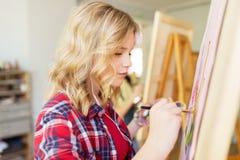 Studentflicka med stafflimålning på konstskolan Royaltyfri Fotografi