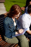 Studentflicka som skriver till anteckningsboken på universitetsområdet Royaltyfri Fotografi