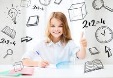 Studentflicka som studerar på skolan Arkivbild