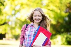 Studentflicka som tillbaka går till skolan och att le Arkivfoto