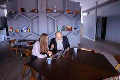Studentflickan förklarar hur man använder bärbara datorn till professorn, ger advic royaltyfri foto