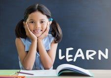Studentflickan på tabellen mot den blåa svart tavla med lär text Royaltyfri Foto