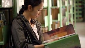 Studentflickasammanträde bredvid bokhyllor och läseböcker lager videofilmer