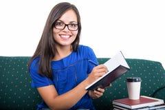 Studentflickasammanträde på soffahandstil i anteckningsbok royaltyfri foto
