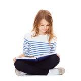 Studentflickastudera och läsebok Royaltyfria Bilder
