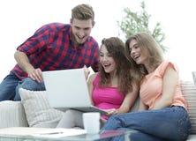 Studentfolk som bläddrar till och med din favorit- video på bärbara datorn arkivbilder