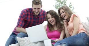 Studentfolk som bläddrar till och med din favorit- video på bärbara datorn arkivfoton