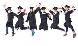 studentgrupp i doktorand- ämbetsdräkt som tillsammans hoppar Arkivfoto