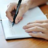 Studenthand med en pennhandstil på anteckningsboken Royaltyfri Foto
