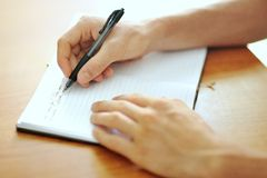 Studenthand med en pennhandstil på anteckningsboken Royaltyfri Fotografi