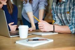 Studenti in abbigliamento casual che studiano insieme e che per mezzo del computer portatile Immagine Stock Libera da Diritti