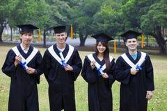 studenti in abiti di graduazione sul campus universitario Immagini Stock