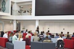 Studenti ad una conferenza nell'atrio dell'università, vista posteriore Immagini Stock Libere da Diritti