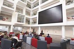 Studenti ad una conferenza nell'atrio di un'università moderna Fotografia Stock